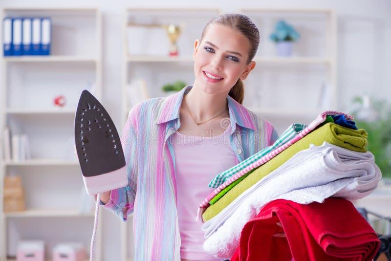 La femme au foyer heureuse faisant repasser à la maison photos stock