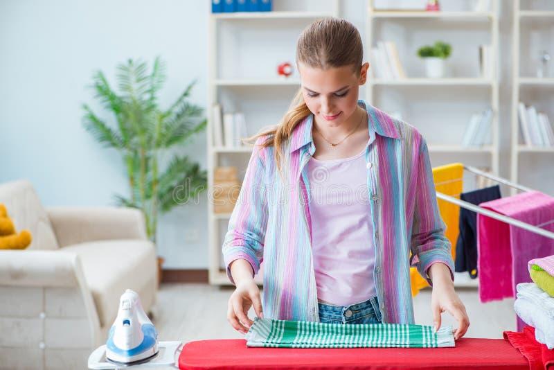 La femme au foyer heureuse faisant repasser à la maison photo libre de droits
