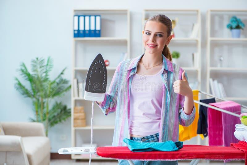 La femme au foyer heureuse faisant repasser à la maison photographie stock libre de droits