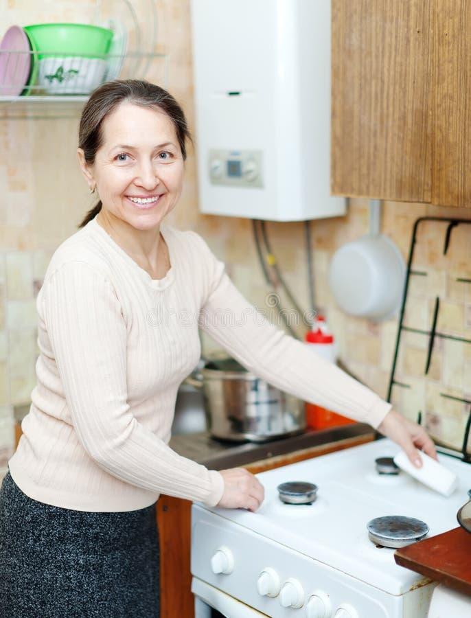 La femme au foyer mûre nettoie la cuisinière à gaz photo stock