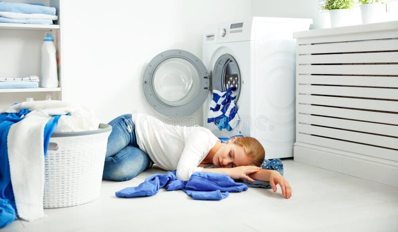 La femme au foyer malheureuse fatiguée de femme est employée dans la blanchisserie, image stock