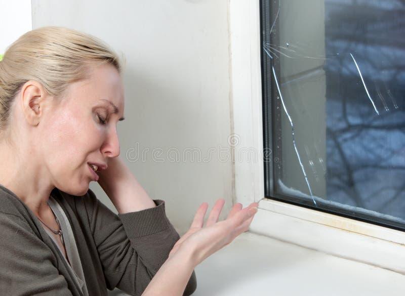 La femme au foyer pleure, mauvaise fenêtre de qualité a éclaté en raison du temps froid photographie stock libre de droits