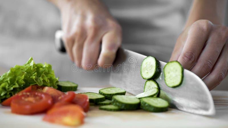 La femme au foyer remet le concombre de coupe sur le panneau de cuisine, salade végétale faisant cuire des étapes photos stock