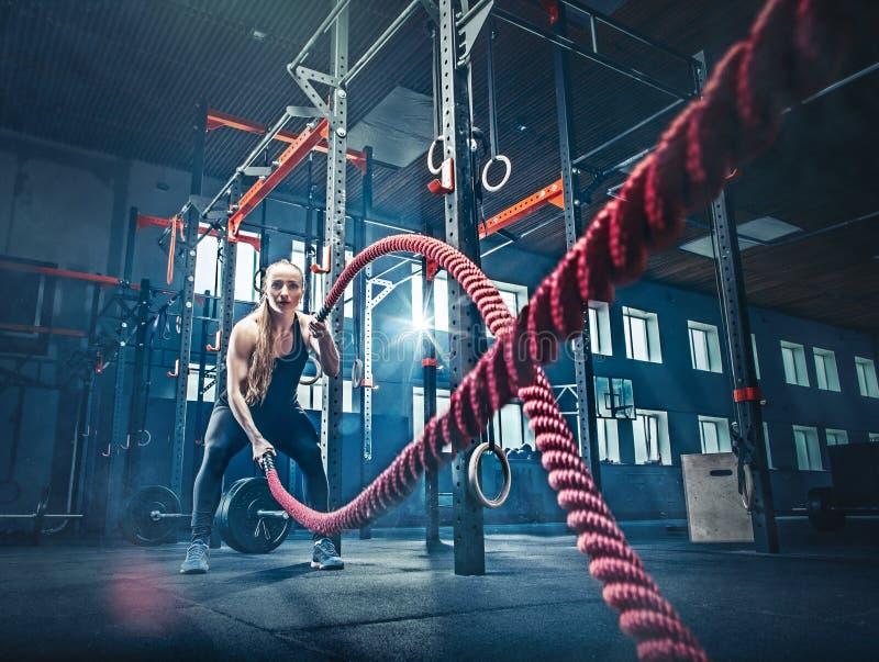 La femme avec la bataille de corde de bataille ropes l'exercice dans le gymnase de forme physique images libres de droits