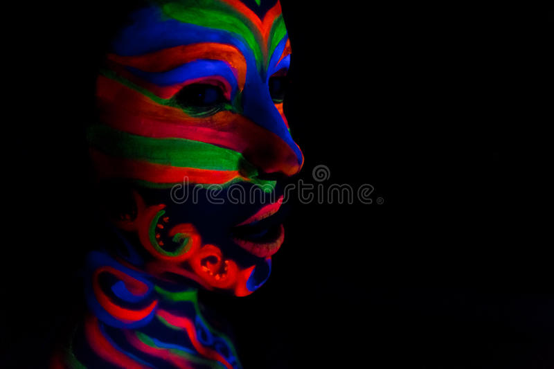 La femme avec composent l'art de la poudre fluorescente UV rougeoyante illustration libre de droits