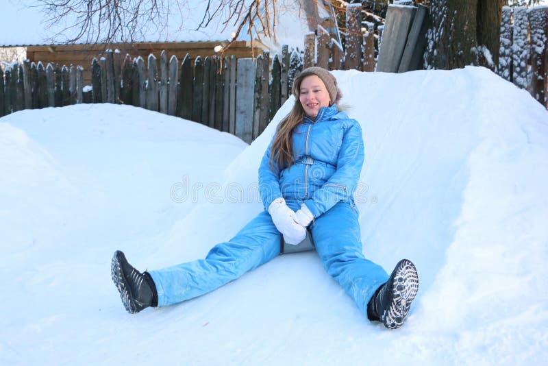 La femme avec de longs cheveux dans un costume bleu glisse de la montagne photographie stock