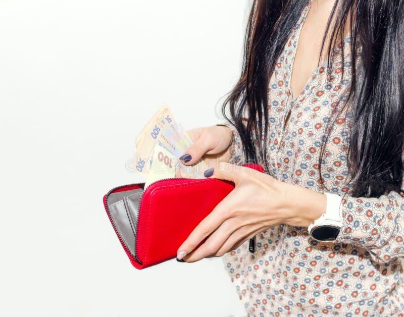 La femme avec de longs cheveux noirs met la monnaie fiduciaire dans une bourse rouge images libres de droits