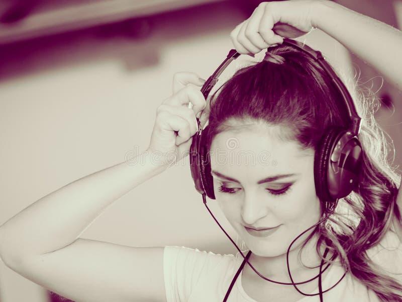 La femme avec des écouteurs écoutent musique et dansent photographie stock