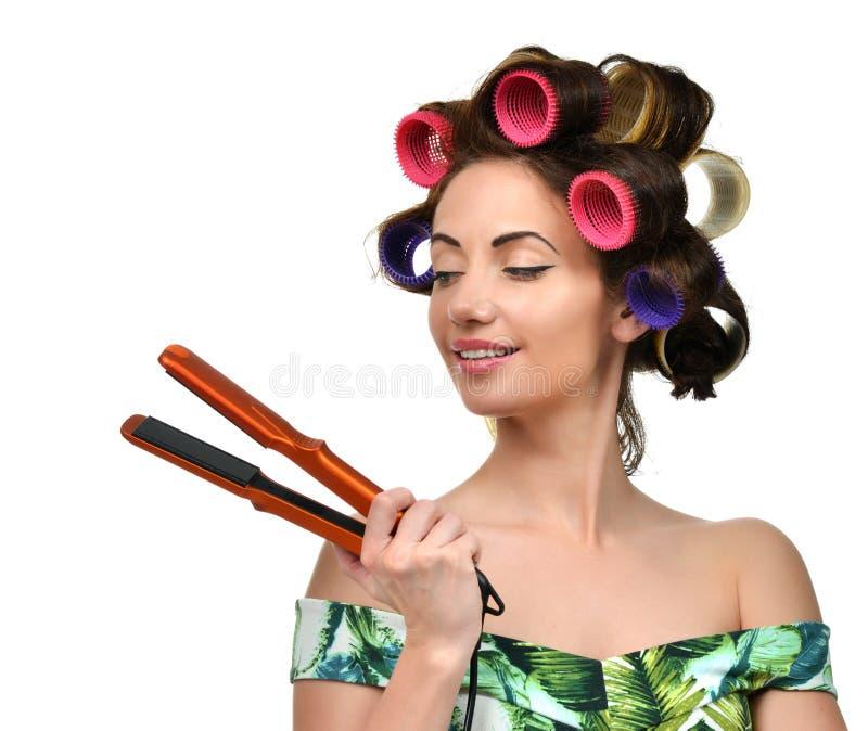 La femme avec des bigoudis tiennent l'outil repassant de bordage de cheveux images libres de droits