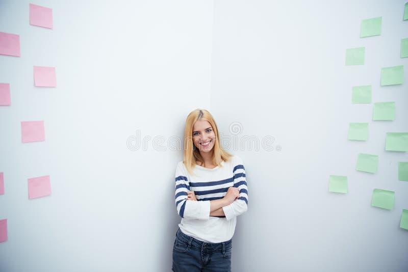 La femme avec des bras a plié la position dans le coin au bureau images stock