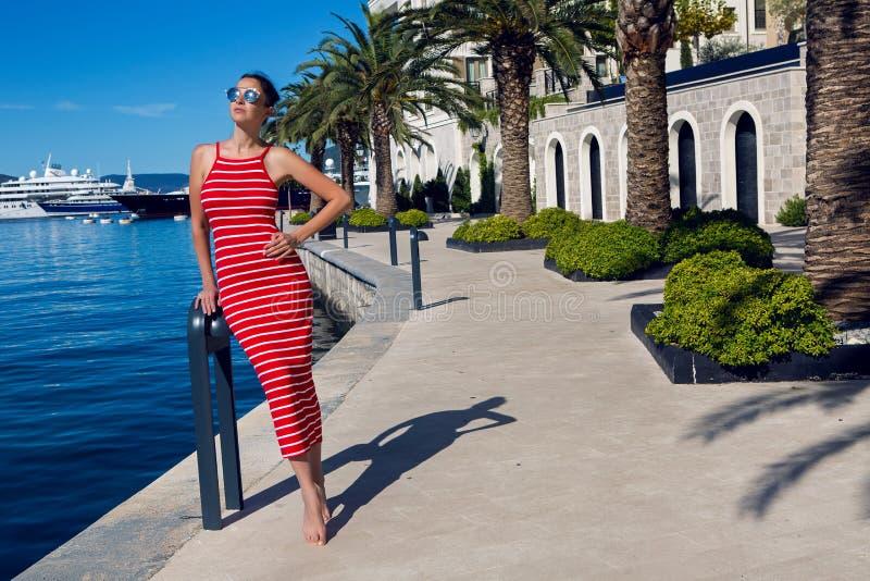 La femme avec des lunettes de soleil se tient sur le pilier parmi images libres de droits