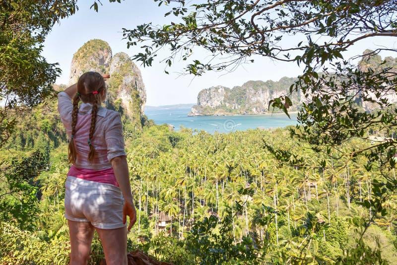 La femme avec des tresses de cheveux dans la chemise rose se tient sur le dessus de la colline et observe au-dessus des jungles e photographie stock
