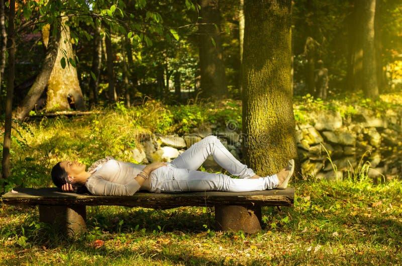 La femme avec des yeux a clôturé la détente sur un banc en nature image libre de droits