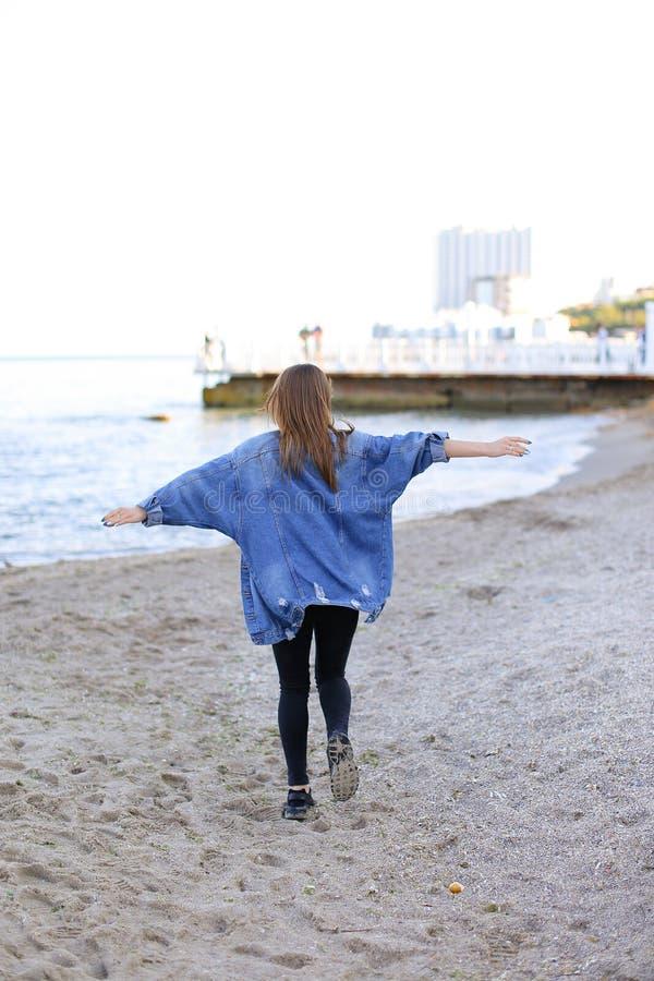 La femme avec du charme avec le sourire pose et marche le long du bord de mer sur la guerre photos stock
