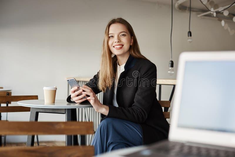 La femme avec du charme reçoit le compliment du type avec l'ordinateur portable Étudiante attirante prenant le déjeuner en café,  photo stock