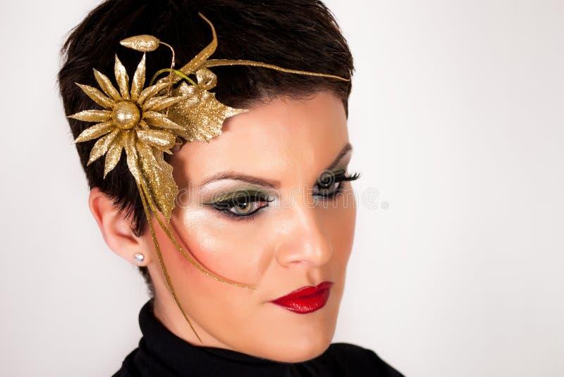 La femme avec l'épingle à cheveux d'or dans les cheveux foncés courts et composent sur le visage photographie stock libre de droits