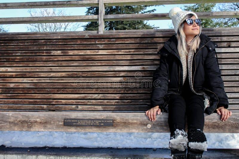 La femme avec l'hiver vêtx, se reposant sur un banc en bois avec la neige photos libres de droits