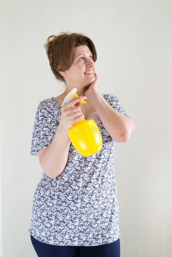 La femme avec la bouteille pour arroser fleurit dans des mains photographie stock