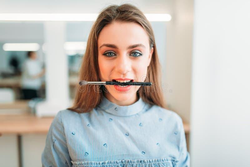La femme avec la brosse dans des dents pose dans le studio de beauté photographie stock libre de droits