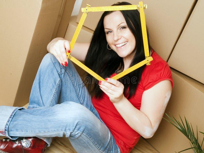 La femme avec le carton enferme dans une boîte la bande de mesure de fixation images libres de droits