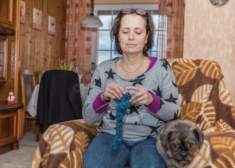 La femme avec le chien s'assied dans le fauteuil et tricote photo libre de droits