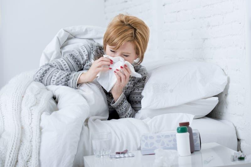 la femme avec le nez de éternuement soufflant dans le tissu sur le lit souffrant des symptômes froids de virus de grippe ayant de photographie stock