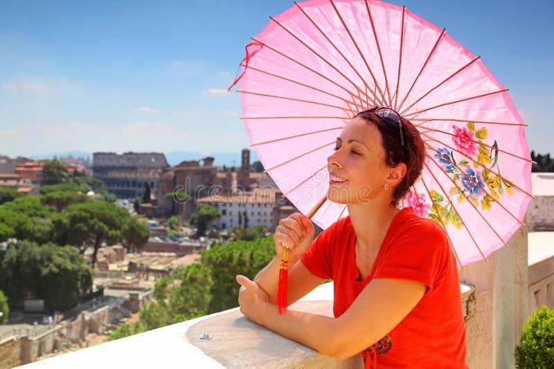 La femme avec le parapluie rose regarde la ROM photos libres de droits