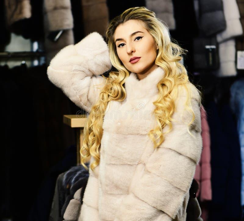 La femme avec les cheveux blonds achète le manteau velu Concept riche de mode Madame essaye le pardessus blanc cher de sable photos stock