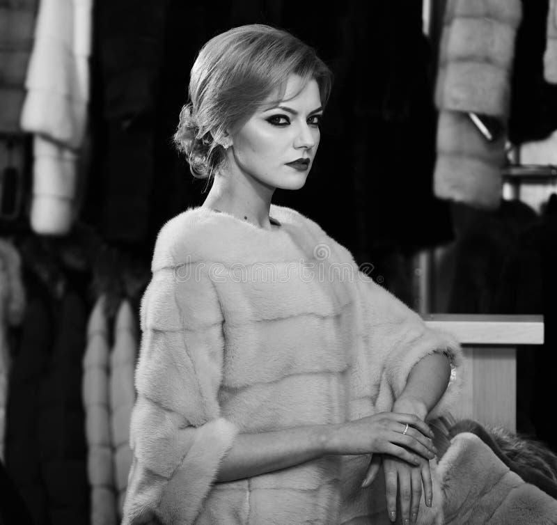 La femme avec les cheveux blonds achète le manteau velu Madame essaye le pardessus rose cher de vison photo libre de droits
