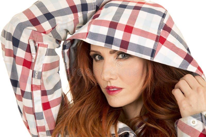 La femme avec les cheveux rouges dans la fin de capot de plaid remet  photographie stock libre de droits