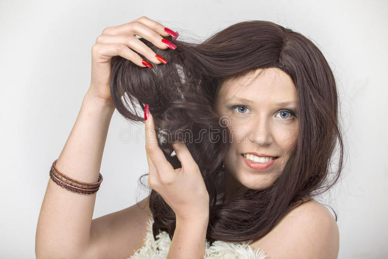 La femme avec les clous rouges a démontré une perruque photographie stock libre de droits