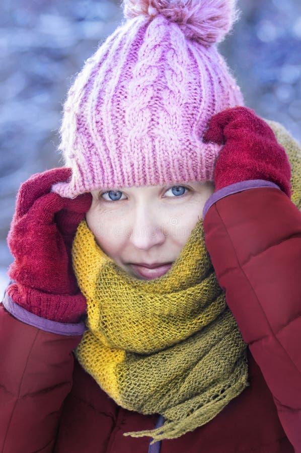 La femme avec les gants rouges et l'écharpe jaune ont chaudement vêtu d'un froid photographie stock libre de droits