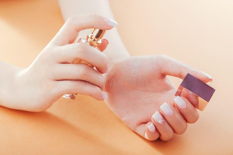 La femme avec la manucure française d'ombre applique le parfum sur son poignet Scincare Cosmétiques image stock