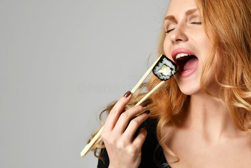 La femme avec la prise Philadelphie de sushi roule dans des mains avec des baguettes sur un gris-clair image libre de droits