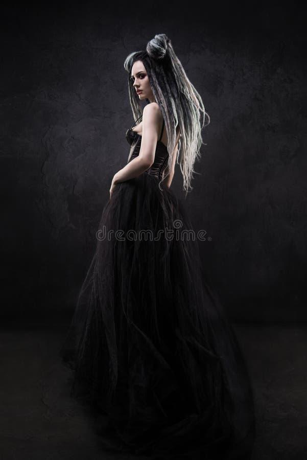 La femme avec redoute et robe gothique noire image stock