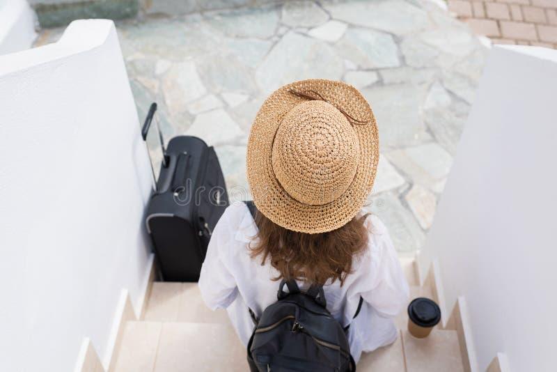 La femme avec la tasse de valise, de chapeau de paille et de papier de café s'assied sur les étapes et les attentes les propriéta images stock