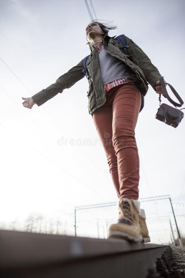 La femme avec un appareil-photo et un sac à dos derrière elle marche avec confiance image libre de droits