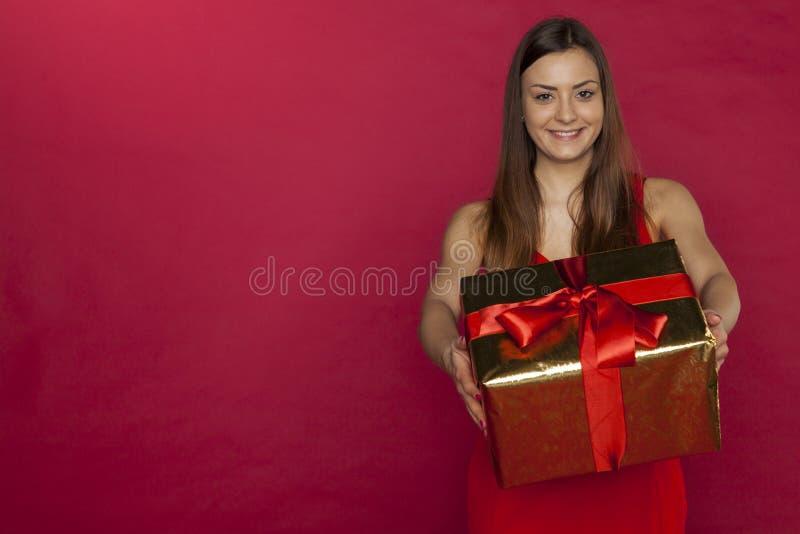 La femme avec un grand cadeau de Noël, te le donnent image stock