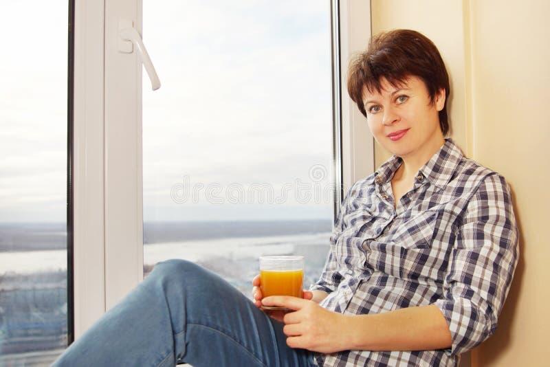 La femme avec un verre de jus s'assied sur le rebord de fenêtre photos stock