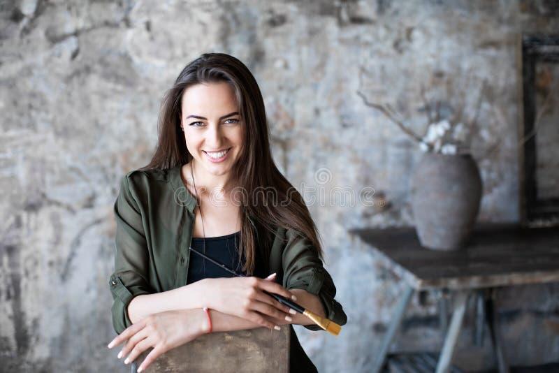 La femme avec une brosse dans sa main et un sourire avec du charme sur son visage a photographié la séance sur une chaise dans un images stock
