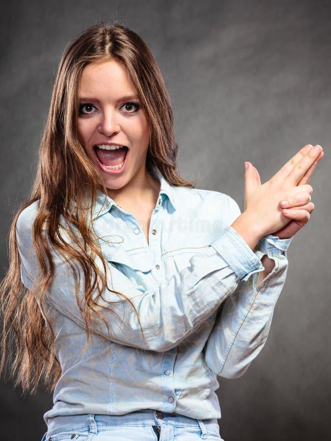 La femme ayant l'amusement feignant le doigt de main est une arme à feu images libres de droits