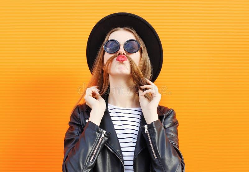 La femme ayant l'amusement montre des cheveux de moustache au-dessus d'orange photographie stock