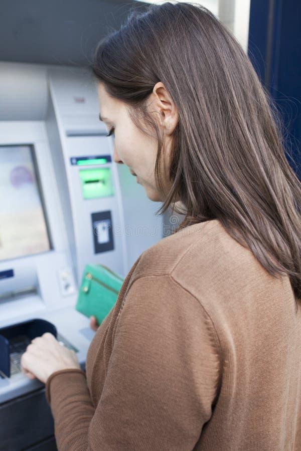 La femme introduit le numéro de borne au mashine d'argent liquide photos stock