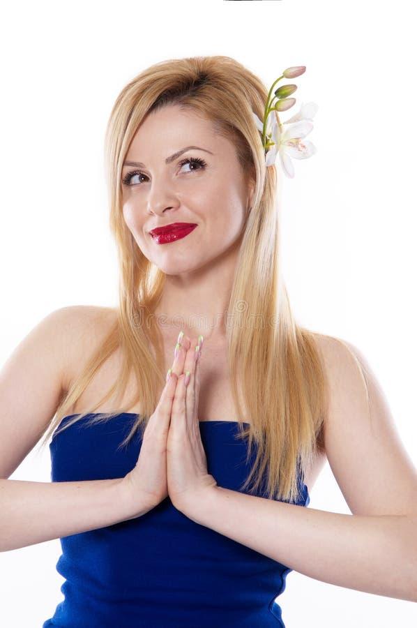 La femme blonde avec de longs cheveux jugeant une orchidée de fleur d'isolement photo stock