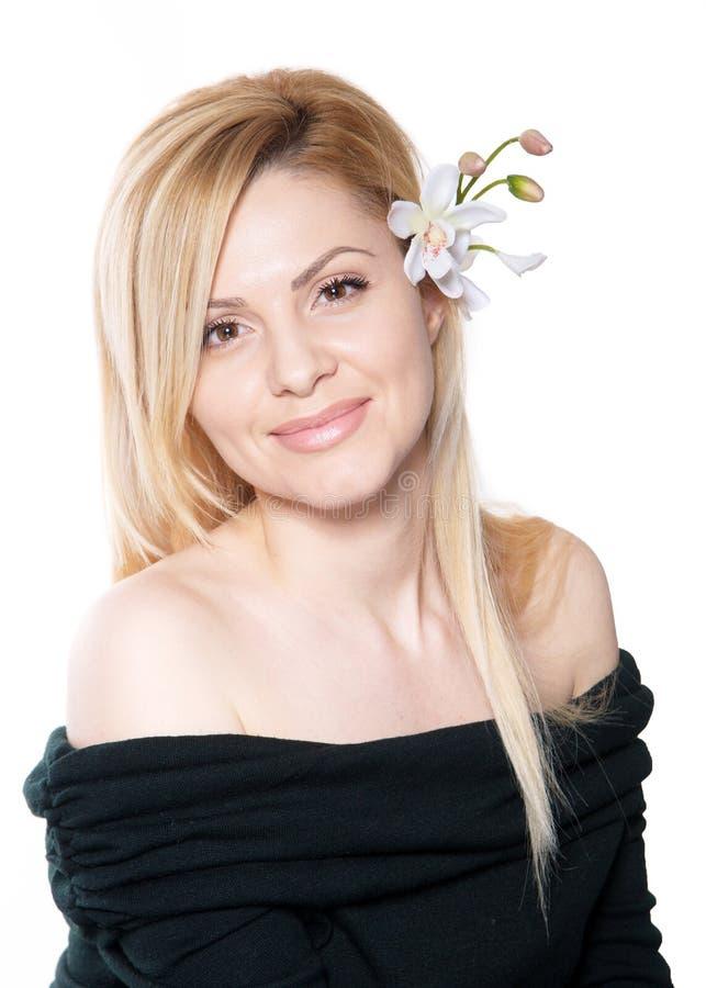 La femme blonde avec de longs cheveux jugeant une orchidée de fleur d'isolement photographie stock libre de droits
