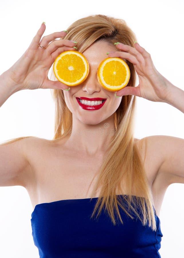 La femme blonde avec de longs cheveux tenant la moitié d'une orange photographie stock