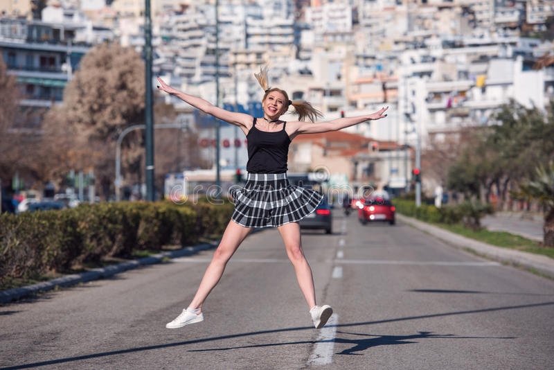 La femme blonde avec de petits tresses sautent au milieu d'une voie rapide photo stock