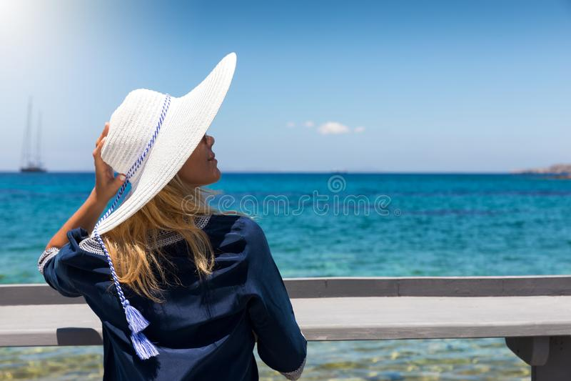 La femme blonde avec le chapeau blanc apprécie ses vacances d'été à la mer bleue image libre de droits