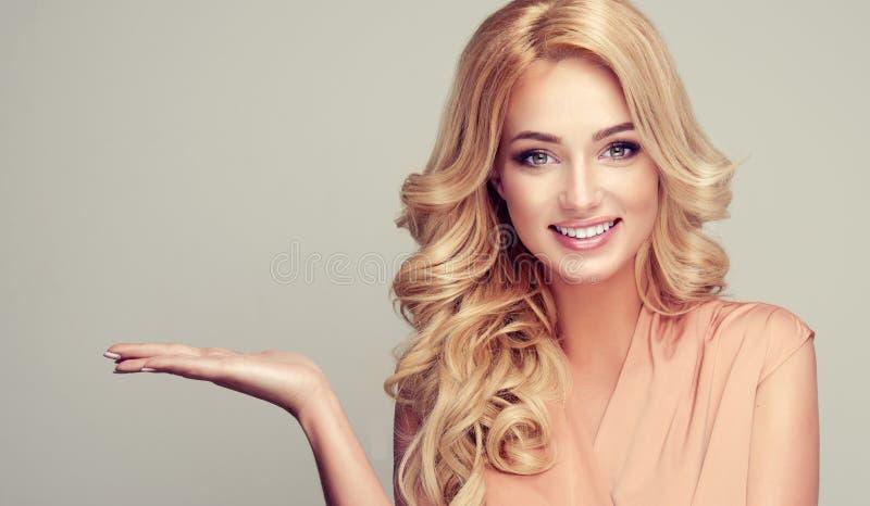 La femme blonde avec les cheveux bouclés démontre votre produit images stock