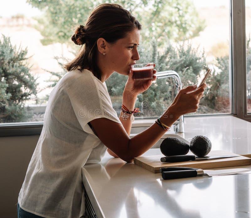 La femme blonde avec les yeux verts dans la cuisine moderne prend un jus de fruit tout en vérifiant ses messages au téléphone photos stock